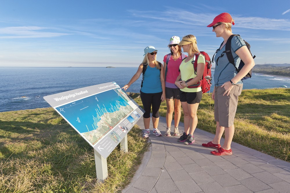 Solitary Islands Coastal Walk. Shows walkers gathered around sign along the coastal walking path in Woolgoolga.